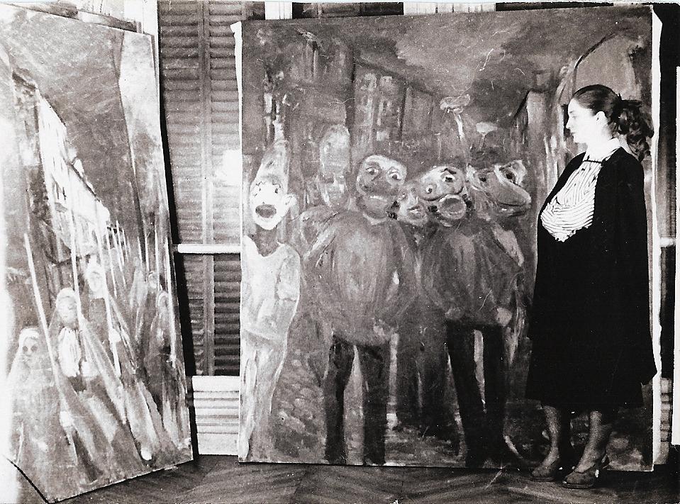 """Colette Bonzo dans son atelier parisien en 1952, avec deux de ses tableaux peints la même année : à gauche, """"Les Communiantes rouges"""", à droite """"Le Carnaval"""" (photo Jean-Pierre Cambier)."""
