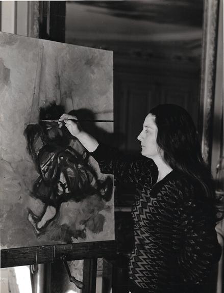 """Colette Bonzo dans son atelier parisien en 1962. Sur le chevalet """"Le Polichinelle"""" (photo Cauvin)."""
